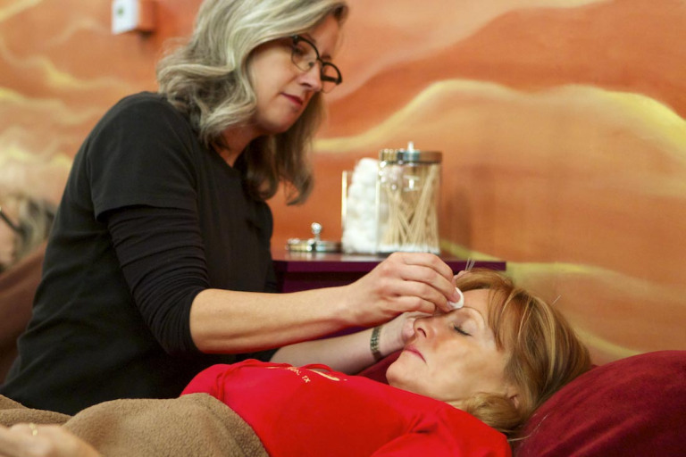 PatchWork Collective Member, Darlene Berger preparing a client for an acupuncture treatment.